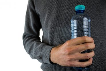 This shows a man holding a plastic water bottle