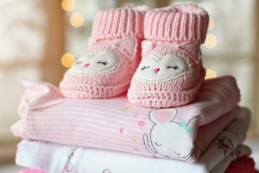 This shows pink baby booties and pink baby blankets