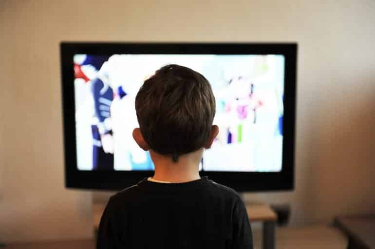 This shows a little boy watching TV