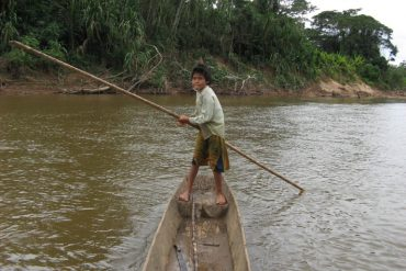 This shows a boy in a canoe