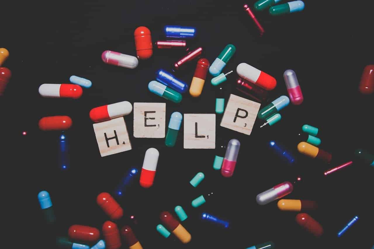 """This shows different colored pills and scrabble tiles spelling out """"help"""""""