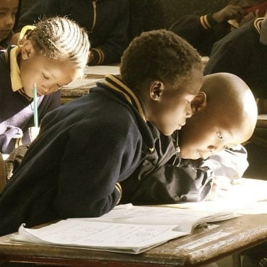 This shows a little school boy curiously looking at his neighbor's work book