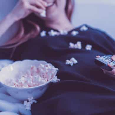 This shows a woman with a remote control and eating popcorn