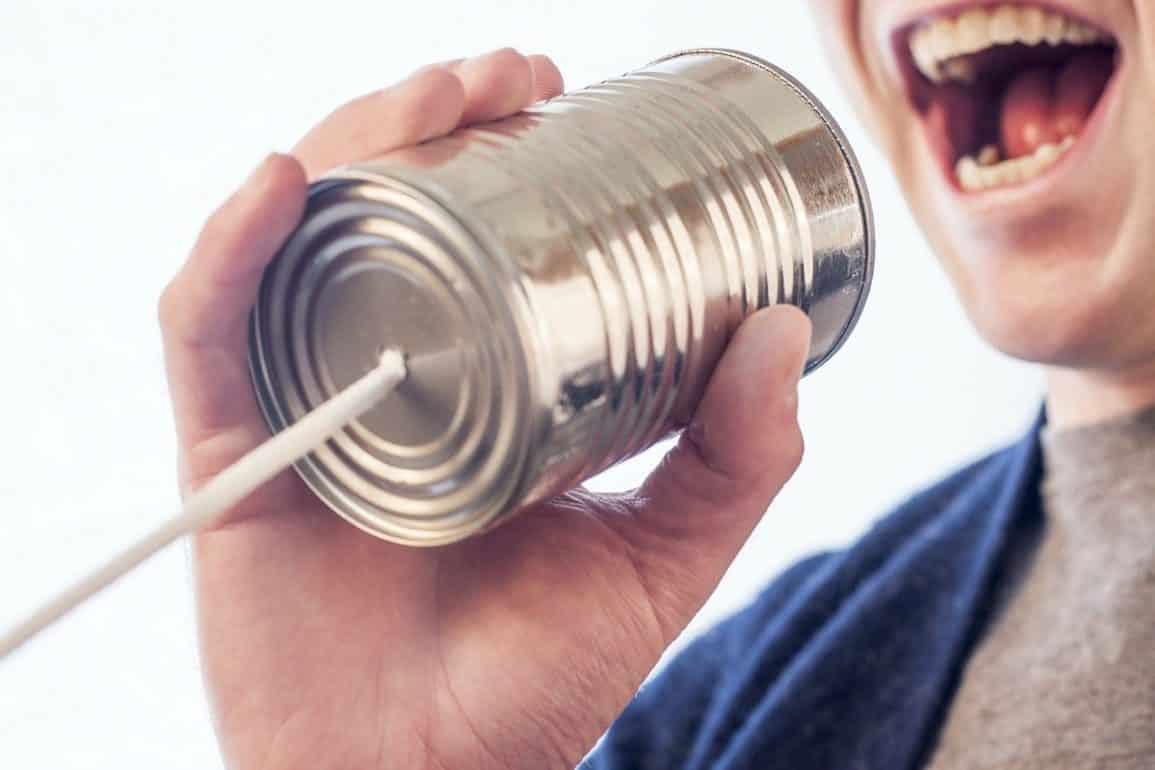"""This shows a man yelling into a tin can """"telephone"""""""