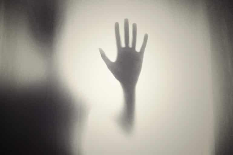 This shows a shadowy hand pressed against a foggy window
