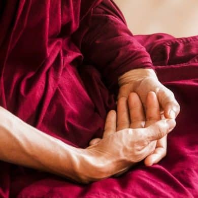 This shows an older person's hands crossed in meditation