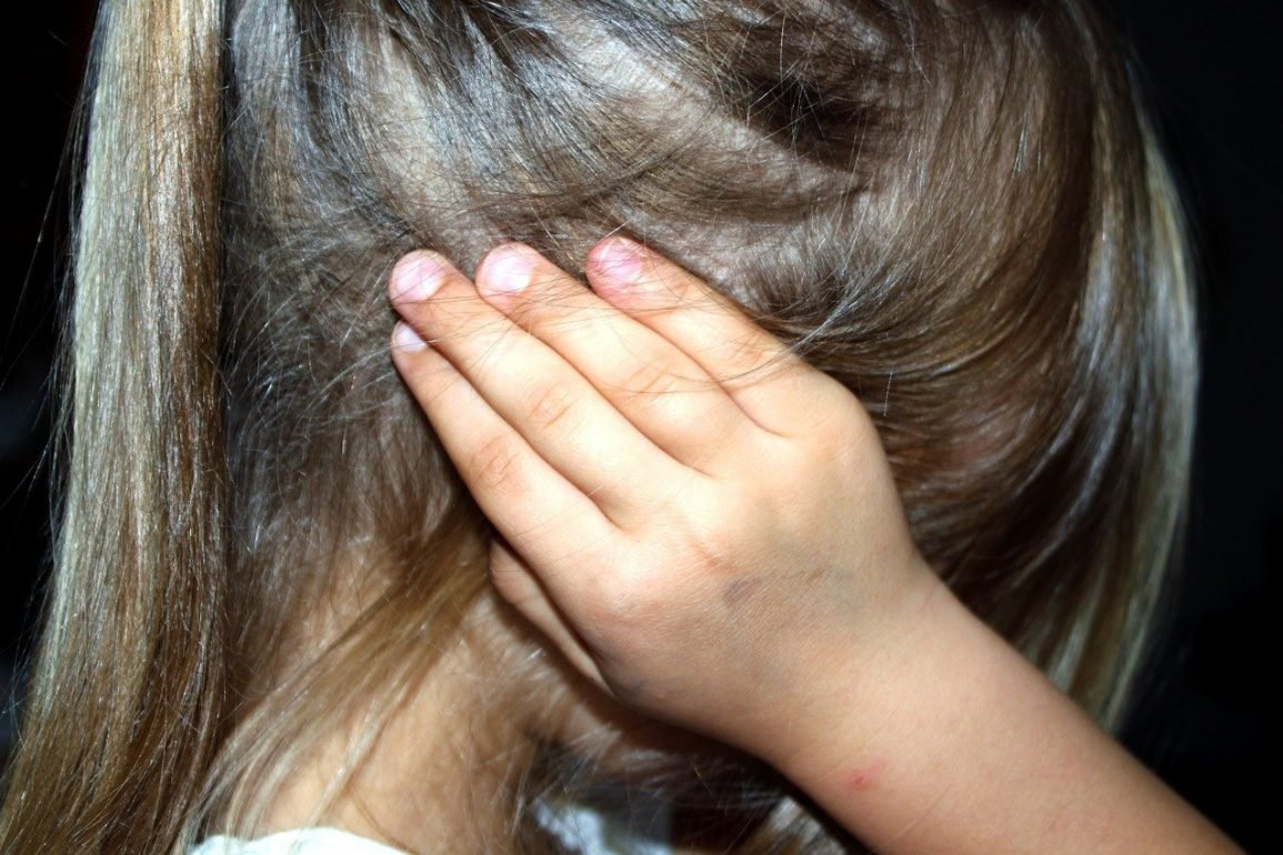This shows a little girl covering her ears