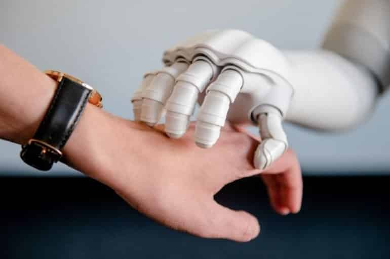 This shows a robot hand resting on top of a person's hand