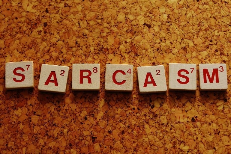This shows the word Sarcasm written in scrabble tiles