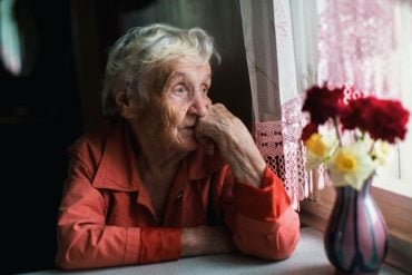 This shows an older lady sitting at a window