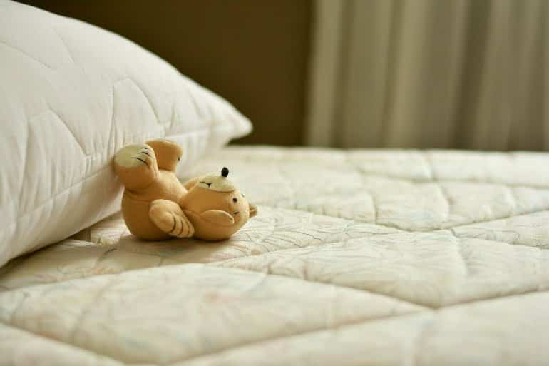 This shows a teddy bear on a bed