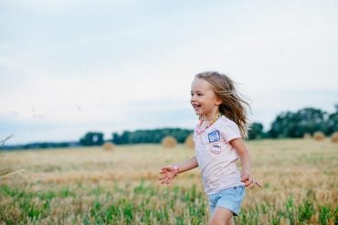 This shows a child running in a field
