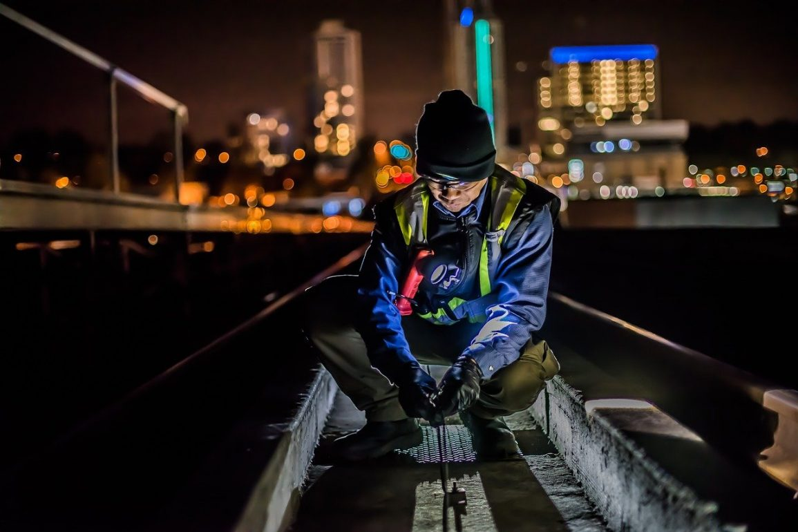 This shows a man working on some rail tracks at night