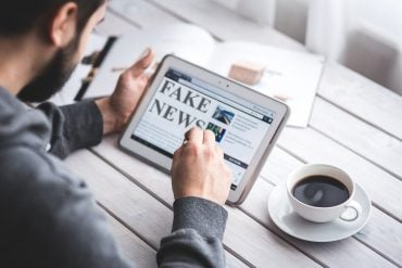 This shows a person looking at a computer tablet with fake news written on it