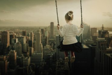 This shows a young girl swinging