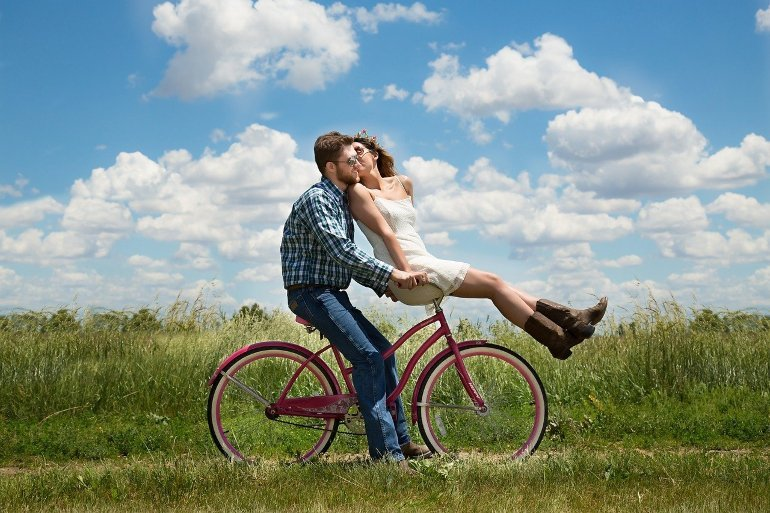 This shows a happy couple riding a bicycle