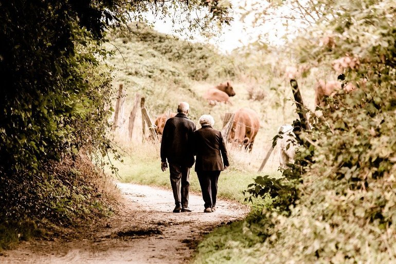 This shows an older couple taking a walk in the countryside