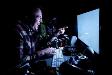 This shows a man laughing at a computer screen