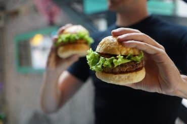 This shows a man holding two burgers