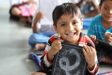 This shows a happy little boy with a chalk board