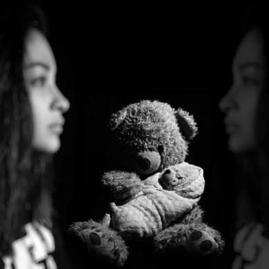 This shows a woman and a teddy bear