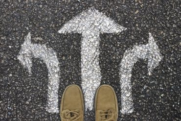 This shows a pair of men's shoes and arrows on a road