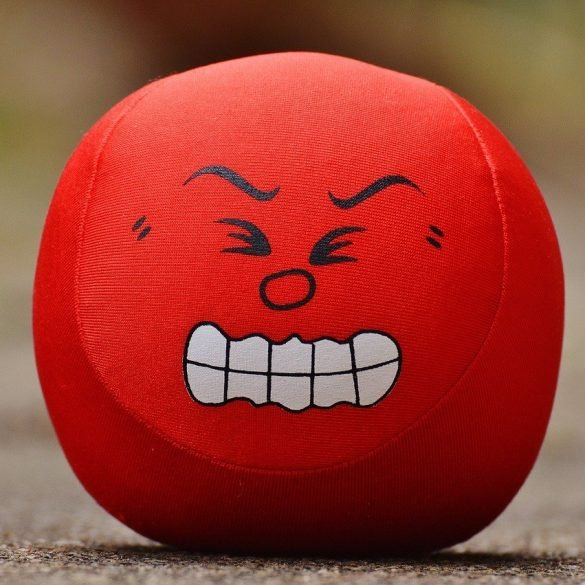 This shows a red ball with a sour looking face painted on it