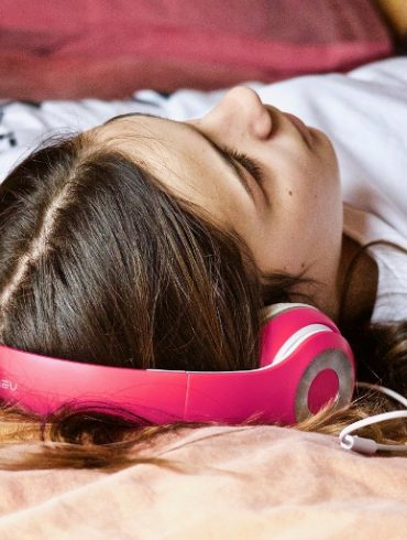 This shows a young girl laying down with headphones on