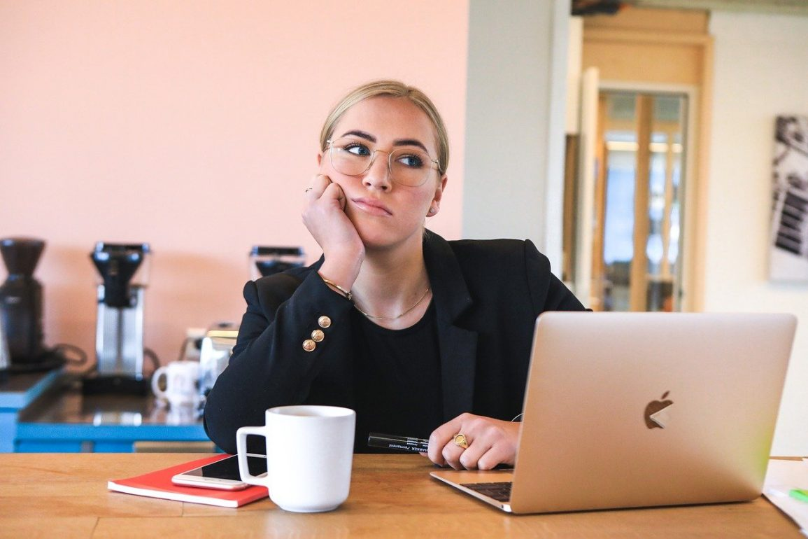 This shows a bored looking business woman sitting at her laptop