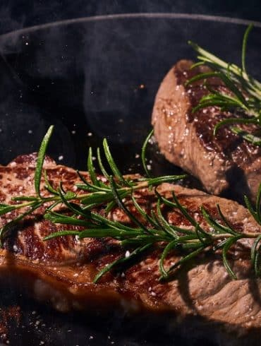 This shows two, juicy steaks in a pan