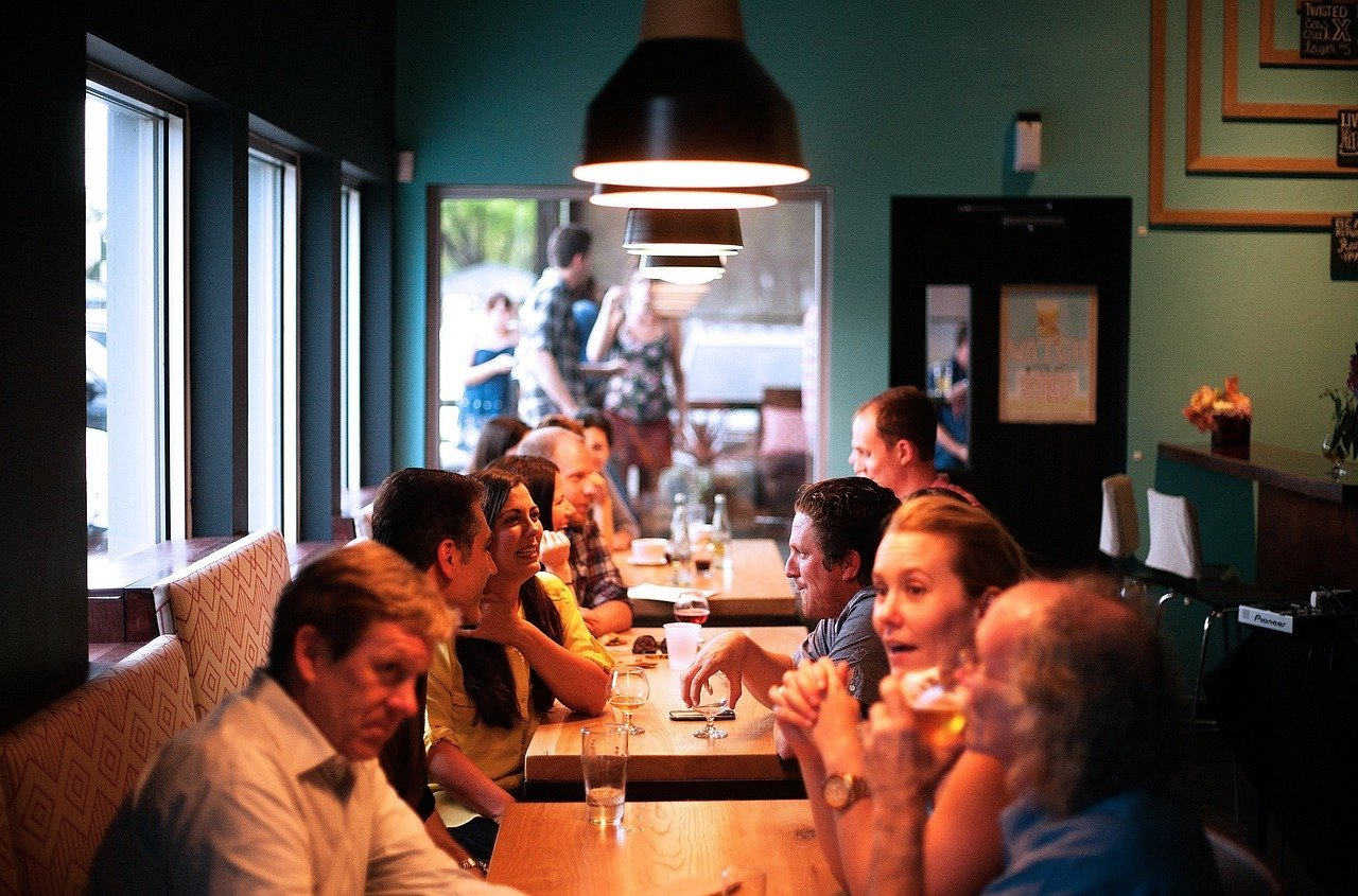This shows people chatting around a table in a restaurant