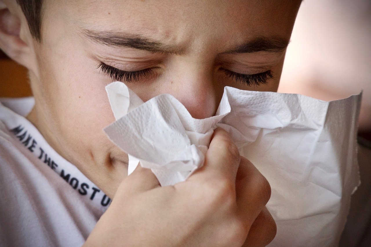 This shows a boy sneezing into a tissue