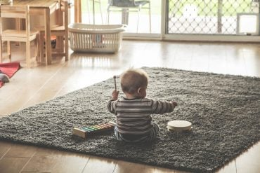 This shows a toddler playing with a toy drum