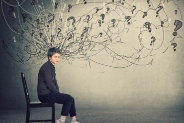 This shows a woman sitting on a chair, surrounded by swirly lines and question marks