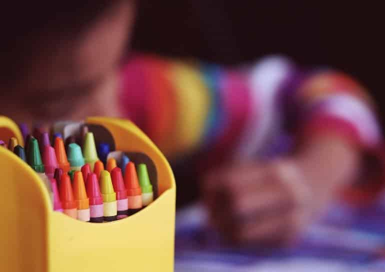 This shows a child drawing with crayons
