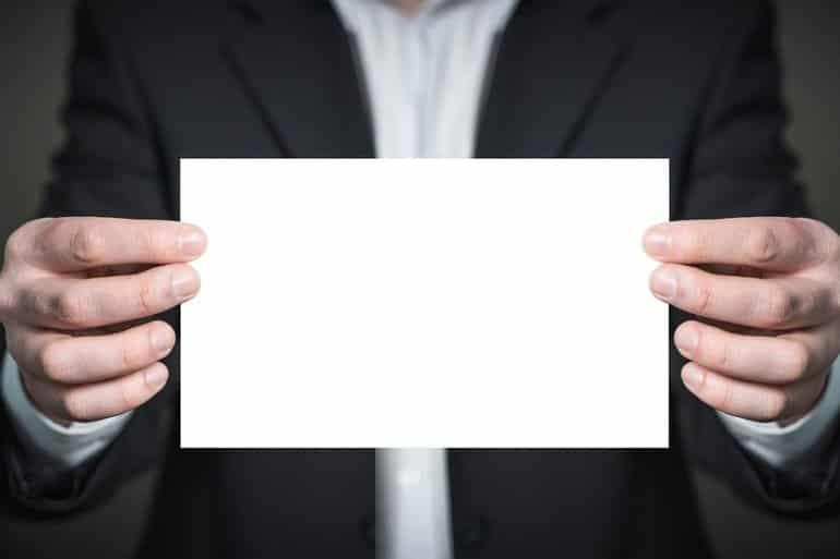 This shows a man holding a blank piece of paper