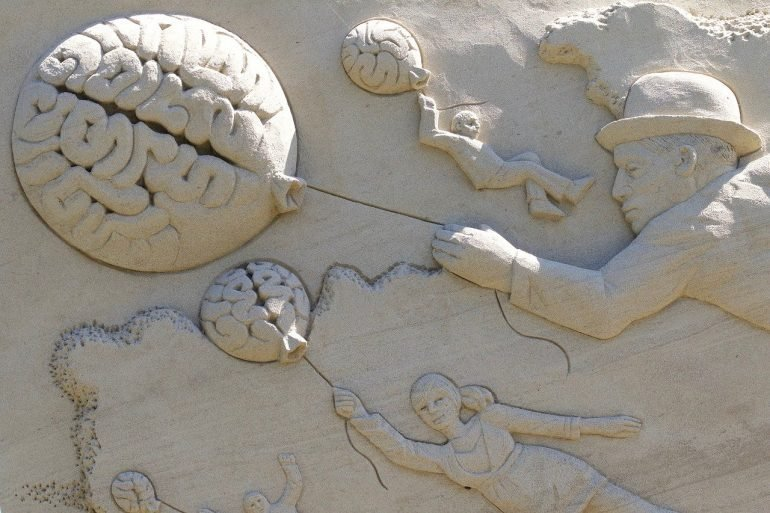 This shows a sand sculpture of a family holding brain shaped balloons