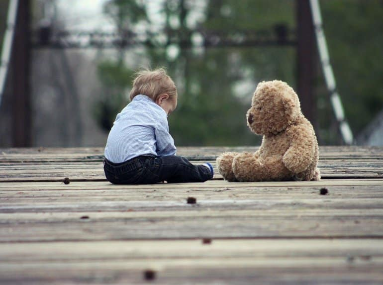 This shows a toddler and a teddy
