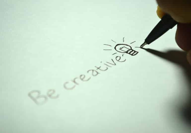 """This shows a piece of paper with """"be creative"""" and a lightbulb drawn on it"""