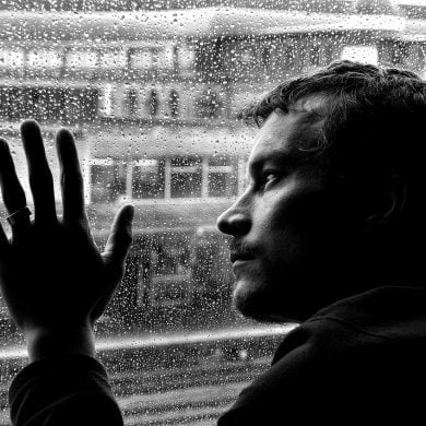 This shows a depressed looking man looking out of a rainy window