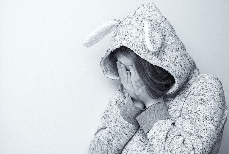 This shows a girl covering her face, looking upset