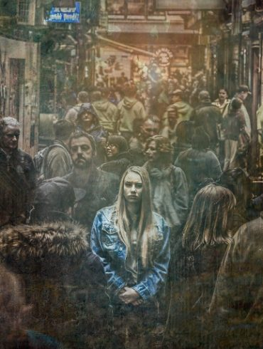 This shows a girl standing alone in a crowd