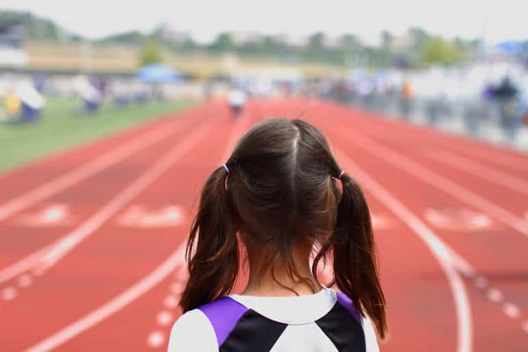 This shows a little girl on a running track