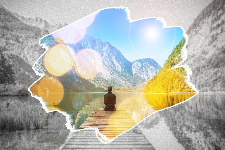 This shows a person sitting on a dock looking at a mountain range