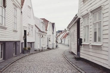 This shows a row of old fashioned white houses on a cobbled street