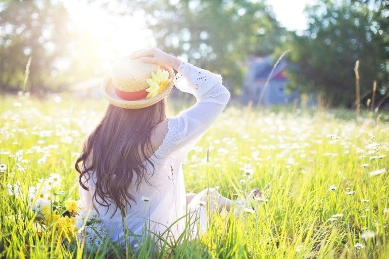 This shows a woman sitting in a field on a sunny day