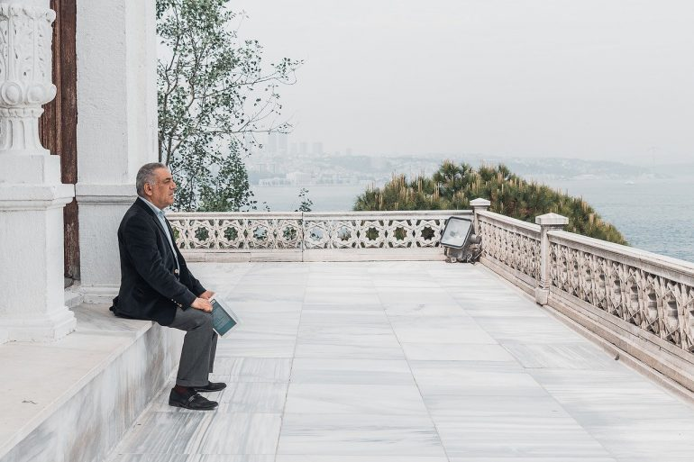 This shows an older man sitting alone