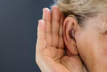 This shows a woman cupping her ear