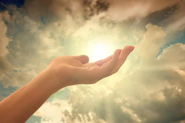 This shows a woman's hand filled with sunlight