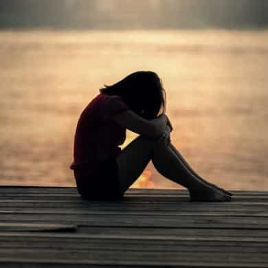 This shows a sad teenage girl sitting on a dock